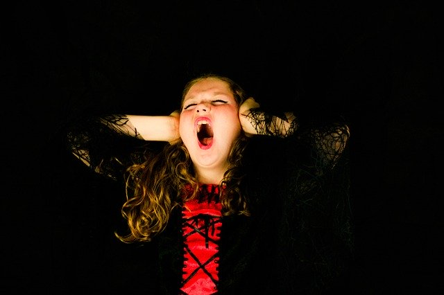 A little girl dressed in black and red with long, curly hair screams with her eyes shut and her hands clamped over her ears.